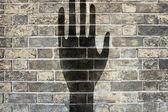 Black hand on brick wall background texture — Stock Photo