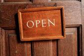 Open sign on old wooden door — Stock Photo