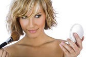 Gorgeous woman applying blush and holding a pocket mirror isolat — Stock Photo