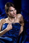 Sexy woman in blue satin sheets — Stock Photo