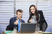 Man and woman in office giving thumbs up — Stock Photo