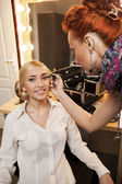 Beauty model getting her make-up done — Stock Photo
