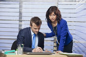 Businesswoman helping businessman with office task — Stock Photo