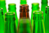 Nine green and one brown bottles. Central brown bottle neck in f — Stock Photo
