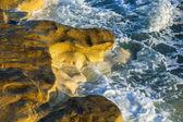 Coastal rocks lapped by the sea surf — Stock Photo