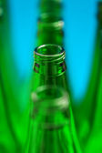 Four green bottles in one row. Bottleneck of central bottle in f — Foto Stock