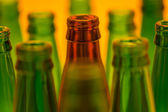 Ten empty beer bottles shot with orange light. Nine green bottle — Stock Photo