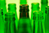 Nine green and one brown bottles shot with green light. Central — Stock Photo