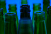 Ten empty beer bottles shot with blue light. Nine green and one — Stock Photo