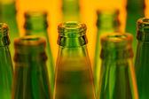 Ten green empty beer bottles shot with orange light. — Stock Photo