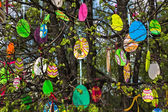 Decorative Easter eggs made of plywood on the tree with young foliage. — Stock Photo