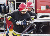 Fire Brigade in action at car accident — Stock Photo
