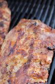 Spareribs on grill with dip and toasted baguette — Stock Photo