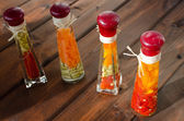 Decorative bottles filled with vegetables and spices — Stock Photo