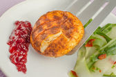 Camembert on grill with cranberries and salad — Stock Photo
