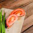Chive with tomatoes on wood plate — Stock Photo #49814973