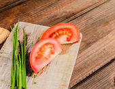 Chive with tomatoes on wood plate — Stock Photo