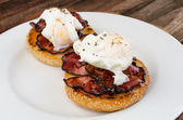 Benedict eggs with crispy bacon and hollandaise sauce on toasted Maffin — Stock Photo