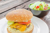 Cheeseburger with bacon and tartar sauce and garden salad — Stock Photo