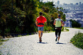 Athletics men running on the trail of the mountain hill and looking the bib city — Stock Photo