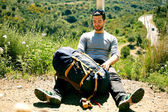 Joven viajero descansando sentado en la colina — Foto de Stock