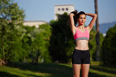 Beautiful athletic girl standing in the green park after the jogging — Stock Photo