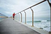 Atlético corredor de pie en el muelle de mar y apartar la mirada — Foto de Stock