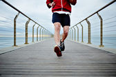 Young athlete man in white t-shirt and sports a red windbreaker runs beach pier — Stock Photo