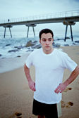 Young athlete man resting after morning jogging on the beach — Stock Photo