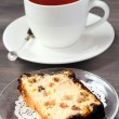 Slice of cheesecake with raisin and candied peel and cup of tea — Stock Photo #46998175