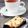 Slice of cheesecake with raisin and candied peel and cup of tea — Stock Photo #46998187