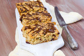 Oat squares with cranberry and chocolate drizzle — Stock Photo