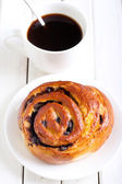 Bun and cup of coffee — Stock Photo