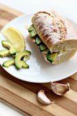 Sandwich on a baguette with avocado, cheese and garlic — Stock Photo