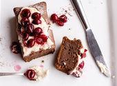 Chocolate cake with cream cheese, raw cherry on white plate — Stock Photo
