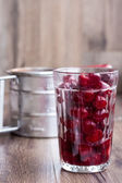 Fresh pitted cherries in a glass — Stock Photo