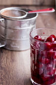 Fresh pitted cherries in a glass, steel cup — Stock Photo