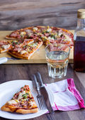 Pizza slices on a plate,  table and a glass of soda — Стоковое фото