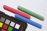 Colored chalks and color cheker — Stock Photo