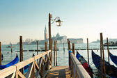 Venice old lantern on the Saint Marco's dock with covered gondolas with an amazing view of  the sea and an island on the background — Stock Photo