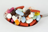 Colourful pills on a spoon — Stock Photo