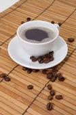 Kaffee mit Kaffeebohnen auf Bambus — Stock Photo