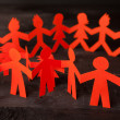 Team of paper doll people holding hands — Stock Photo #47087447