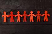 Team van papier pop mensen hand in hand — Stockfoto