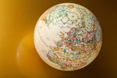 Globe on gold — Stock Photo