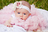Cute newborn girl in pink skirt gnaws fingers — Stock Photo