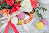 Colored marshmallows, macaroon and a bouquet of flowers — Stock Photo