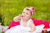 Cute newborn girl smiling on grass in pink skirt with flower — Stock Photo