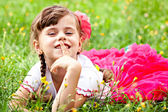 Happy child girl in a pink skirt covers her mouth with a finger — Stock Photo