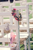 Wedding ceremony chairs and a wreath of roses — Stock Photo